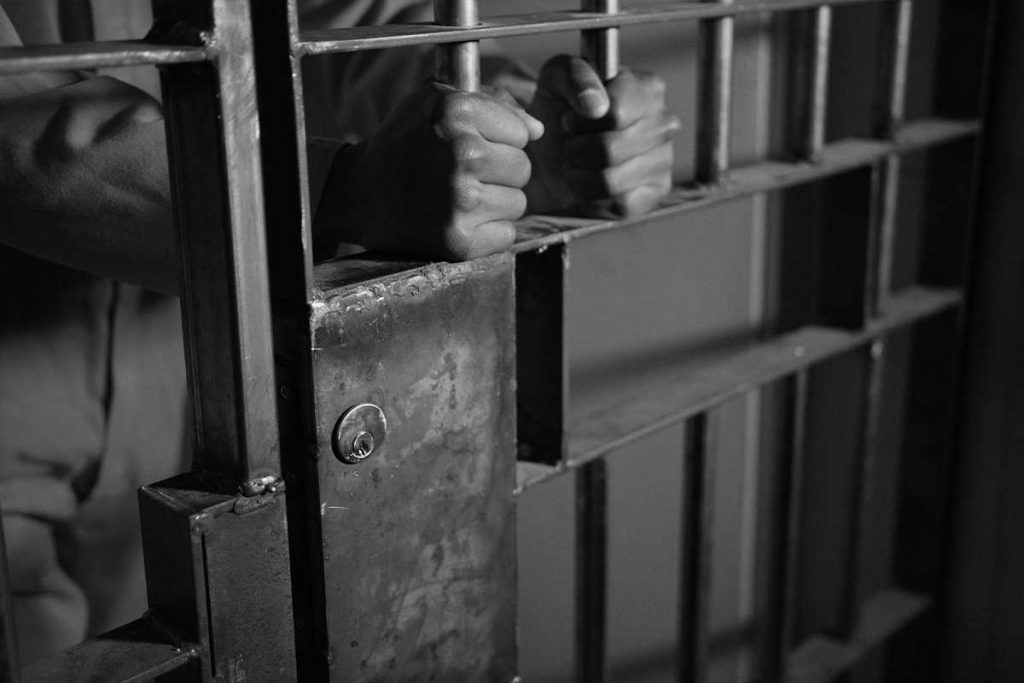 criminal-in-jail-holding-the-bars-of-his-prison-ce-MSRR3XE-cropped
