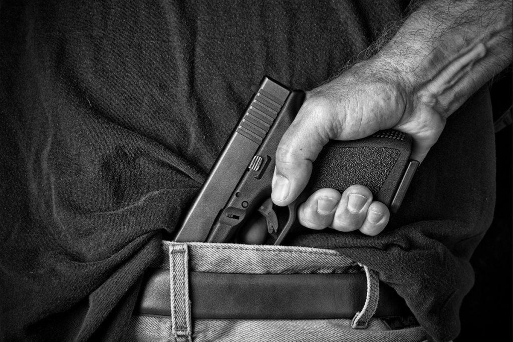 man-pulling-gun-from-waistband