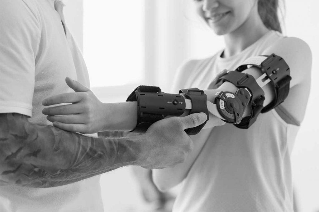 tattooed man putting prosthetics on person